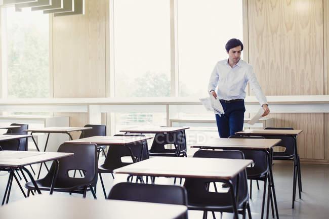 College-Professor sammeln Tests auf dem Schreibtisch im Klassenzimmer — Stockfoto