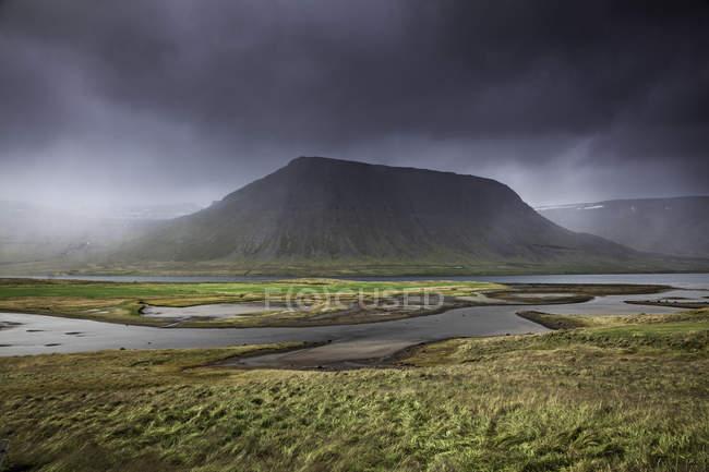 Хилл против прудовой воды и пасмурная погода — стоковое фото