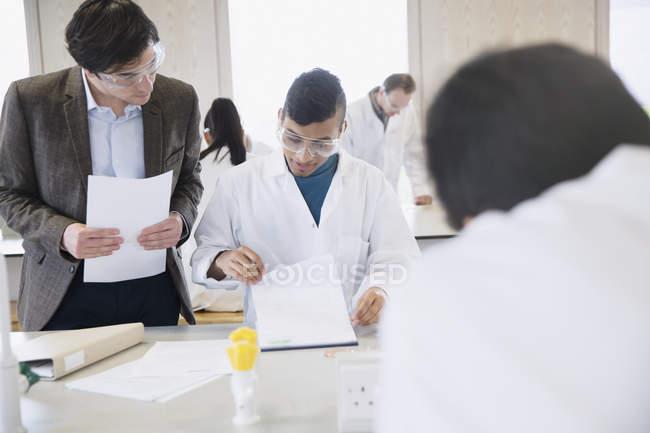 Professore di scienza aiuta studente di college in aula laboratorio di Scienze — Foto stock