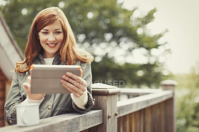 Donna sorridente con i capelli rossi utilizzando tablet digitale e bere caffè a ringhiera balcone — Foto stock
