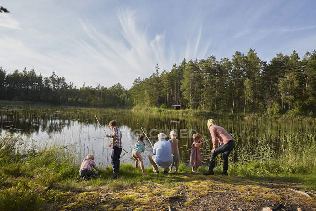 Grandparents and grandchildren fishing at sunny lakeside in woods — Stock Photo