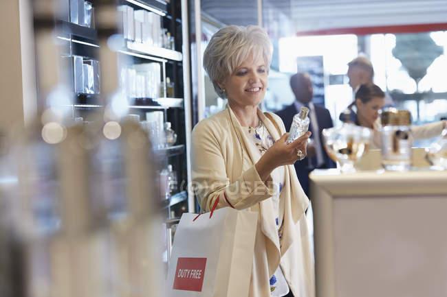Улыбающиеся женщина, ходить по магазинам для духов в магазин беспошлинной торговли — стоковое фото
