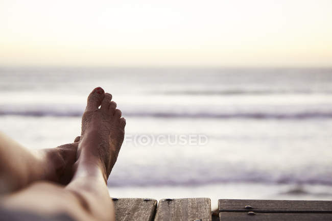 Personal perspective barefoot woman with sand on foot and ocean view — Stock Photo