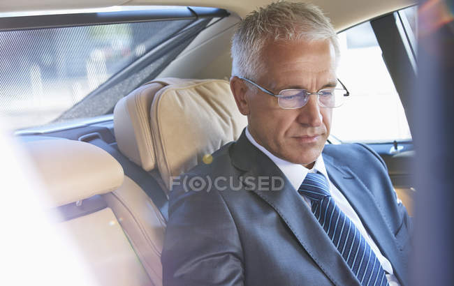 Businessman riding in back seat of town car — Stock Photo