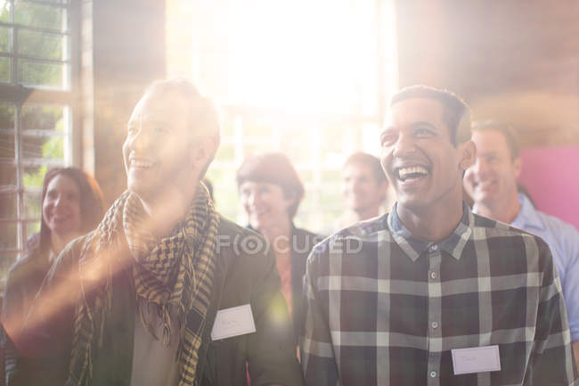 Laughing men in audience at community center — Stock Photo
