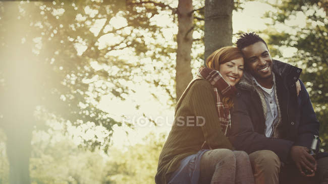 Ласковая пара обнимается и пьет пиво в лесу — стоковое фото