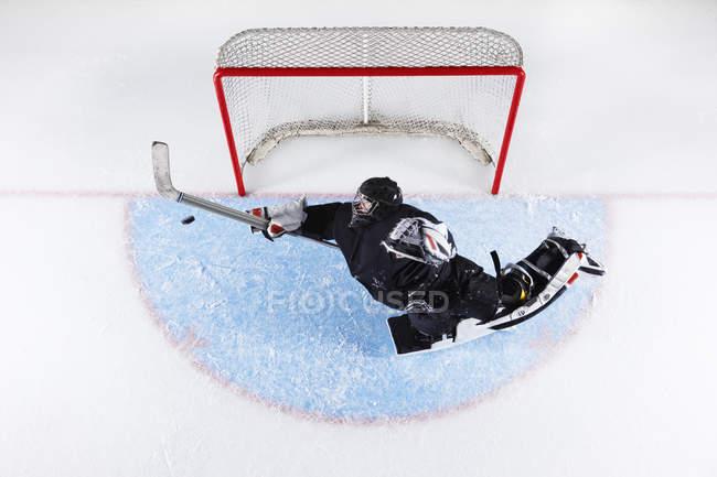 Вид сверху хоккейный вратарь достижения блокировать шайбу на цели сети — стоковое фото