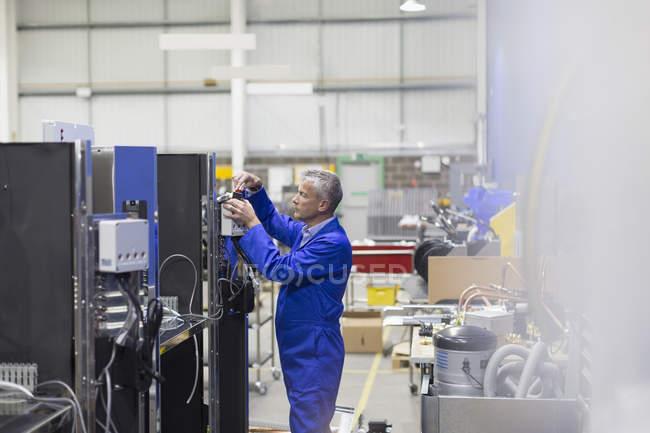 Worker repairing machinery in steel factory — Stock Photo