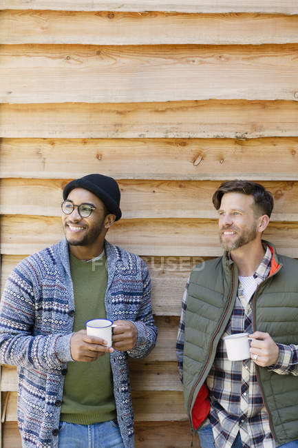 Smiling men drinking coffee outside cabin — Stock Photo