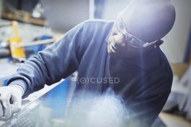 Focused steel worker examining part in steel factory — Stock Photo