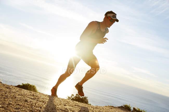 Чоловічий плавця бігун вздовж океану — стокове фото