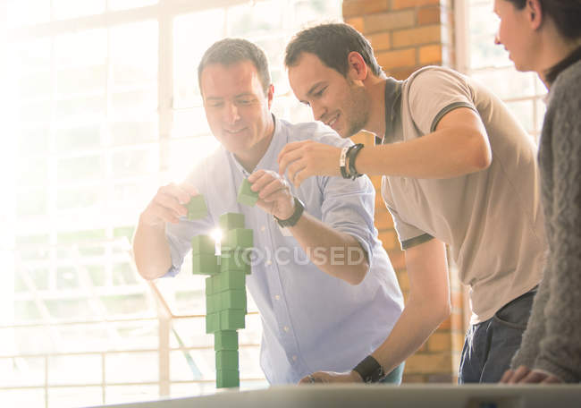 Gli uomini d'affari che equilibrano i blocchi verdi — Foto stock