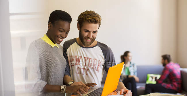 Casual business people sharing laptop in office — Stock Photo