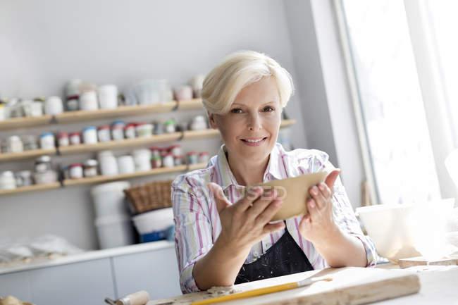 Retrato sonriente tazón de explotación de mujer madura en el estudio de la cerámica - foto de stock