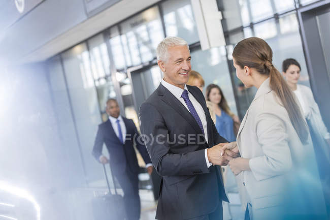 Business people salutation secouant les mains dans l'aéroport — Photo de stock