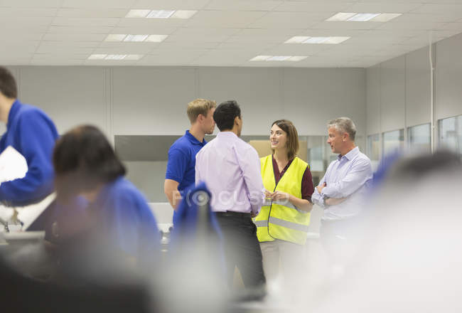 Managers and workers talking in steel factory — Stock Photo