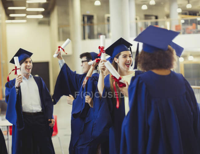 College graduates in cap and gown holding diplomas — Stock Photo ...