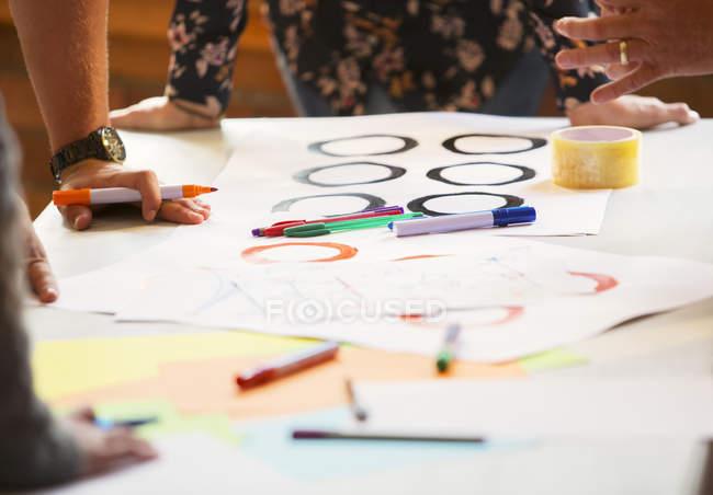 Creativi uomini d'affari che circondano le prove sul tavolo — Foto stock
