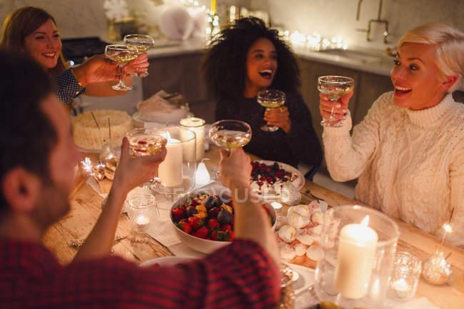 Энтузиазм друзей за бокалы шампанского на рождественском ужине при свечах — стоковое фото