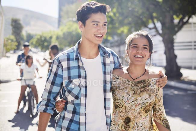 Улыбающаяся пара подростков, идущая по солнечной городской улице — стоковое фото