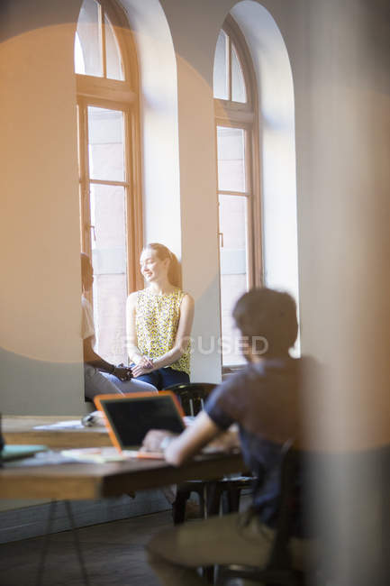 Lens flare over smiling businesswomen talking in office window — Stock Photo
