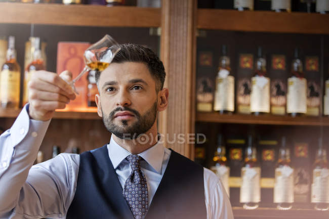 Serious well-dressed bartender examining whiskey — Stock Photo