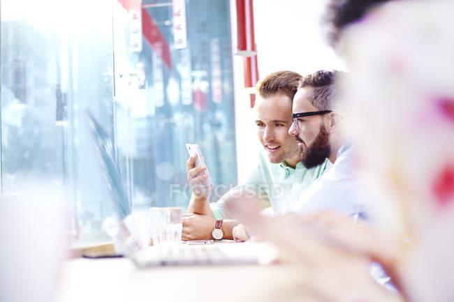 Unternehmer-SMS mit Handy im café — Stockfoto