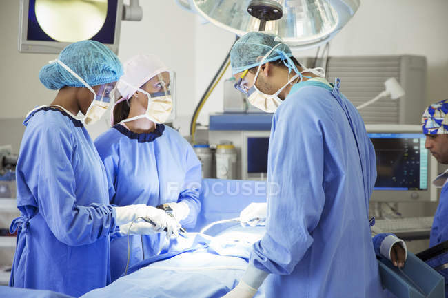 Surgeons performing surgery in operating room — Stock Photo