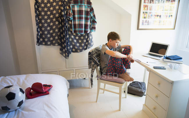 Bored Boy Doing Homework At Desk In Bedroom High Angle View Side Stock Photo 200692466