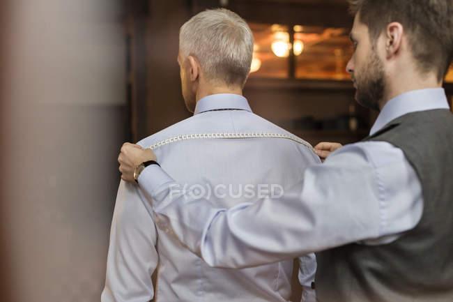 Портной измерения рубашка на бизнесмена с рулеткой в магазин мужской одежды — стоковое фото