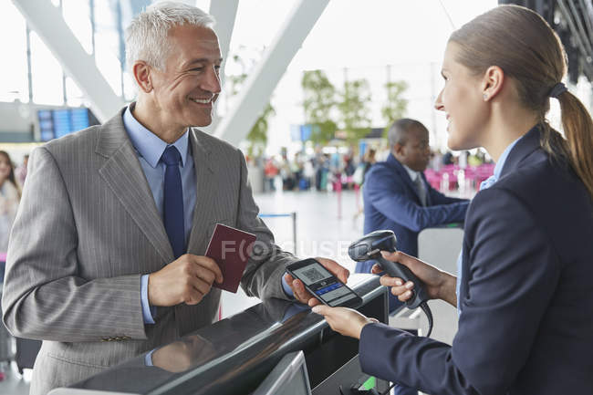 Customer service representative scanning smart phone QR code boarding pass at airport check-in counter — Stock Photo