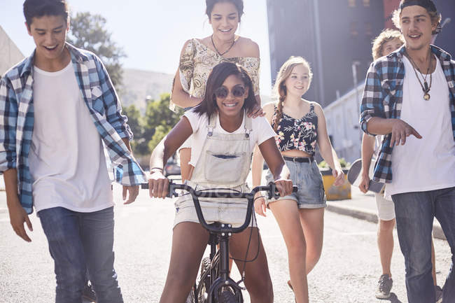 Друзья-подростки с велосипедом BMX на солнечной городской улице — стоковое фото