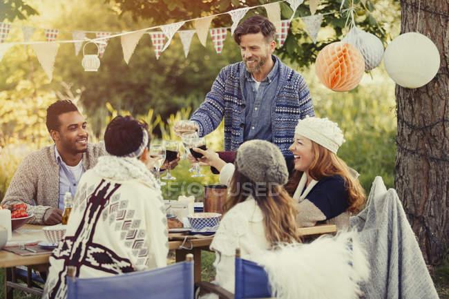 Amigos brindando copos de vinho na mesa de almoço do jardim — Fotografia de Stock
