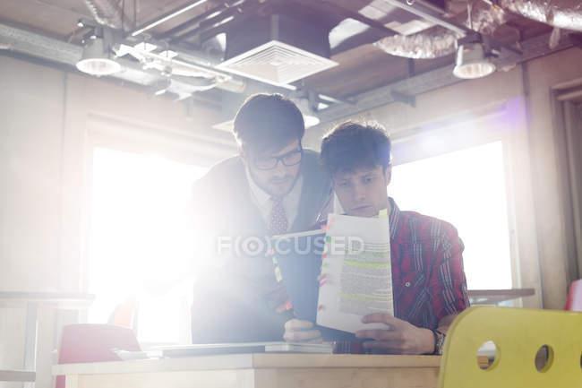 Empresários revendo edições de documento em escritório ensolarado — Fotografia de Stock