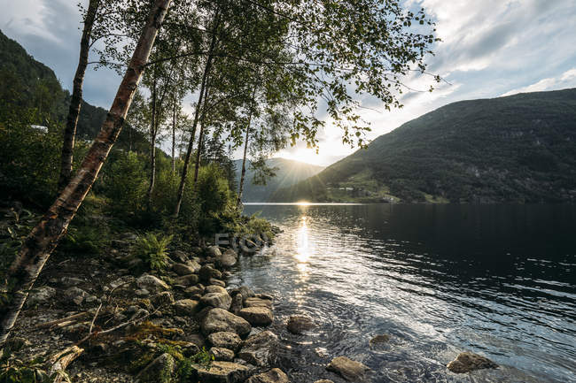 Sun setting over tranquil lake, Norway - foto de stock