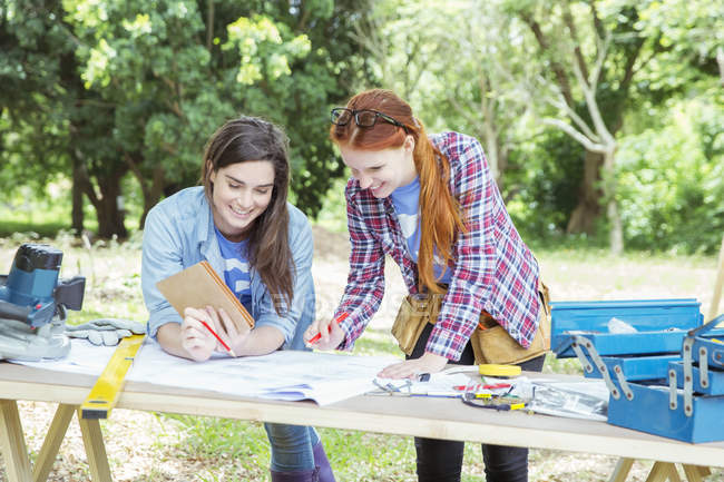 Smiling volunteers reviewing blueprints at construction site — Stock Photo