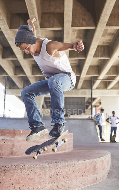 Teenage boy jumping skateboard at skate park — Stock Photo