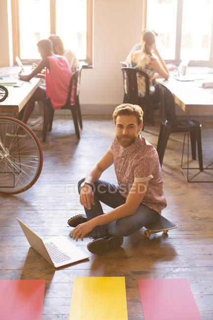 Portrait creative businessman working on laptop on floor — Stock Photo