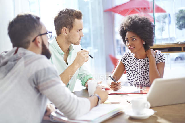 Business people talking in meeting at modern cafe — Stock Photo