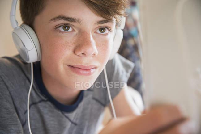 Close up boy con cuffie che ascoltano musica su tablet digitale — Foto stock