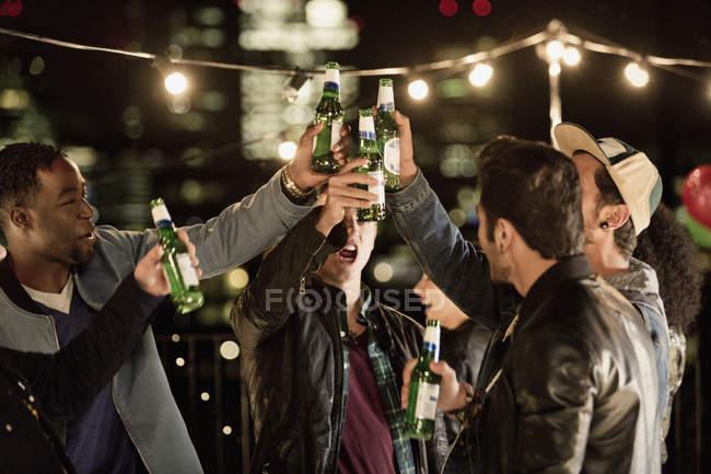 Jovens homens tostando garrafas de cerveja na festa no telhado — Fotografia de Stock