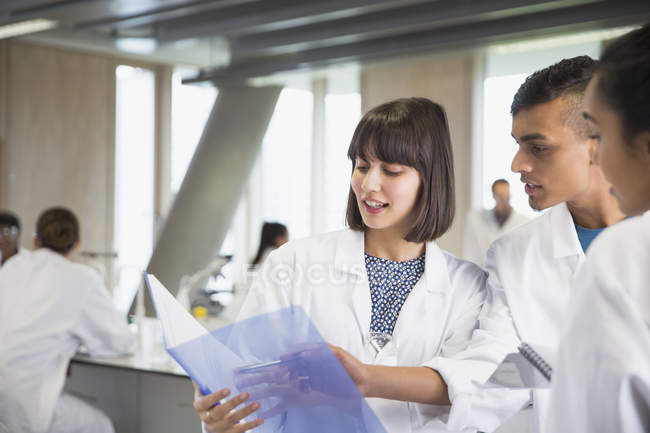 College students discussing notes in science laboratory classroom — Stock Photo
