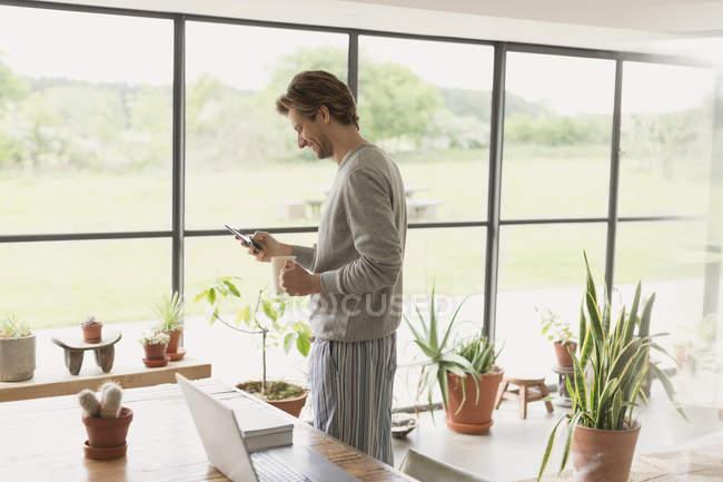 Uomo in pigiama che beve caffè e messaggia con il cellulare — Foto stock