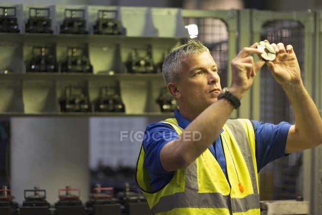 Worker examining part in steel factory — Stock Photo