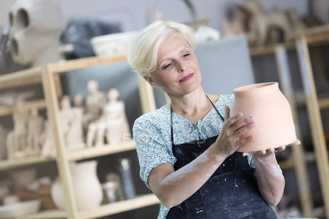 Mature woman holding pottery vase in studio — Stock Photo