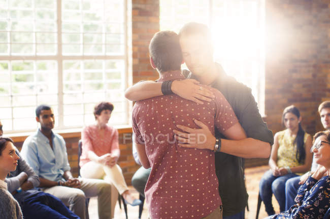 Men hugging at group therapy session — Stock Photo