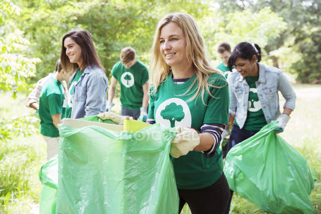 Smiling environmentalist volunteer picking up trash — Stock Photo