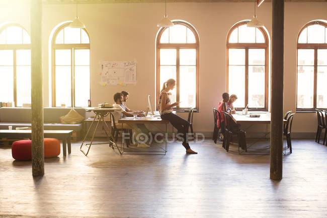Творческие бизнесмены, работающие в солнечном открытом офисе — стоковое фото