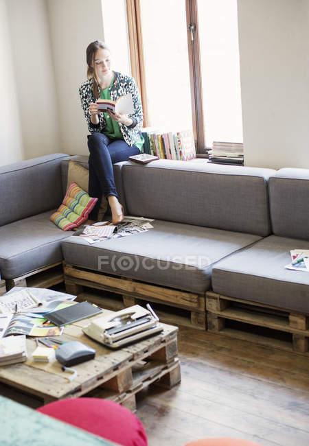 Libro di lettura di donna d'affari creativa a finestra in ufficio — Foto stock