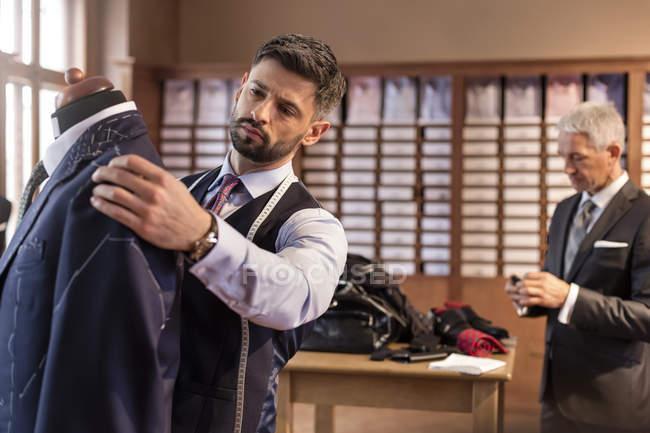 Портной настраивает костюм на модель портнихи в магазине мужской одежды — стоковое фото